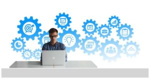 Man on laptop with blue tool icons in background