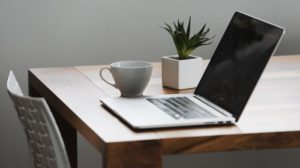 Laptop on table with mug and plant