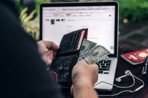 guy pulling out money from wallet in front of laptop