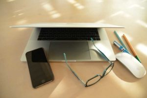 laptop with phone, glasses, mouse, and pens