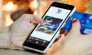 Woman's hands on iphone ecommerce site with credit card in other hand