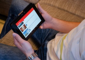 Part of man holding tablet watching YouTube